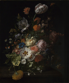 Flowers in a glass vase, on a marble ledge