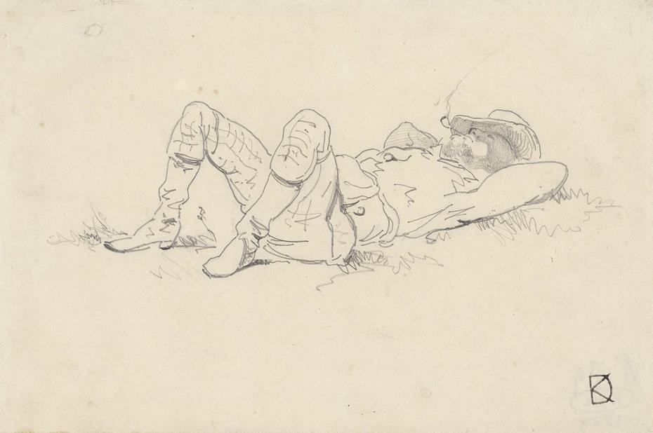Man achterover liggend in het gras met de benen opgetrokken