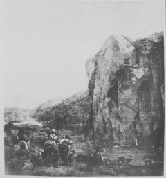 Shepherd watering cattle at the foot of a steep rock wall