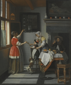 Interior with man drinking and two woman with a child feeding a parrot
