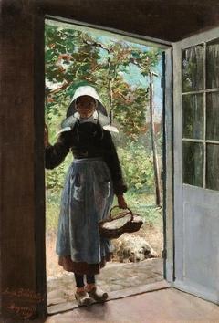 Breton woman standing on a doorstep.