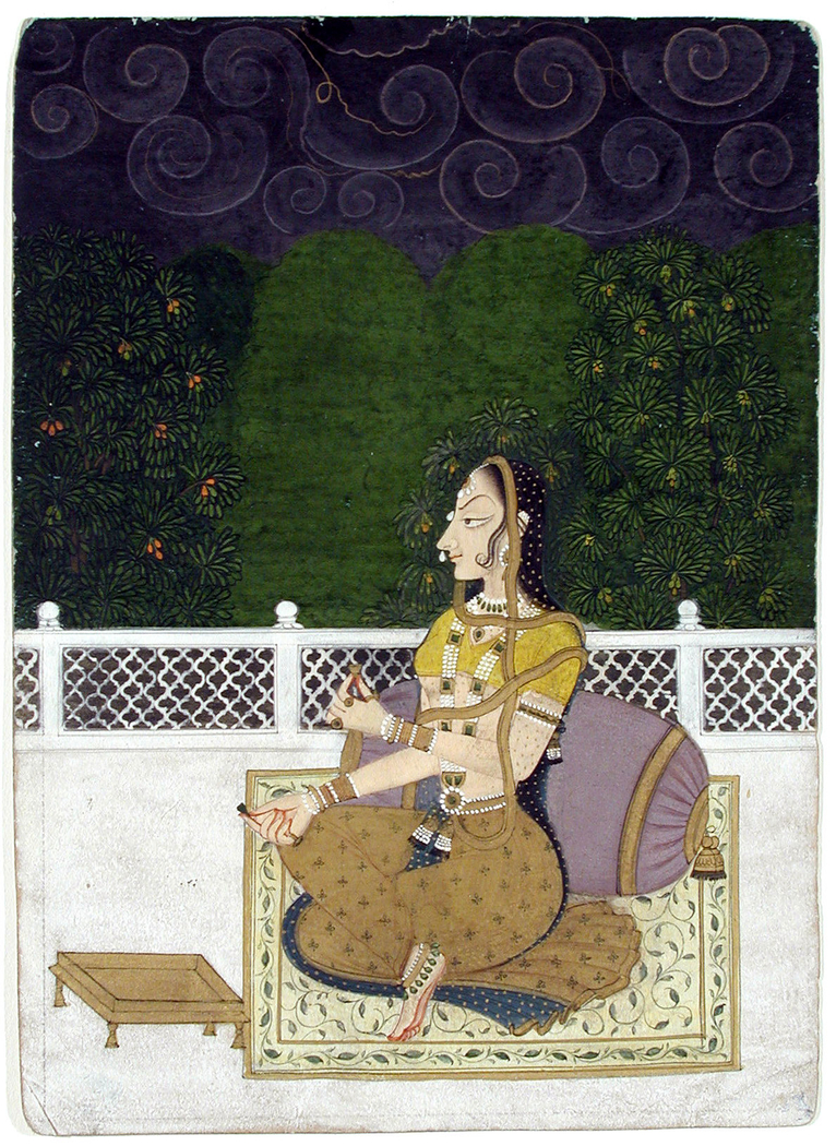 A beautiful woman seated against a bolster