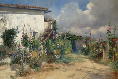 House with hollyhocks in the garden