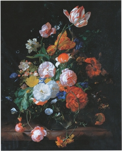 Roses, tulips and other flowers in a glass vase on a marble ledge