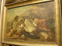 Still life with dead game and fruit in a landscape