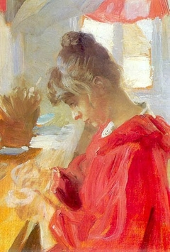 Marie sits at a table sewing