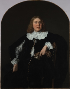 Portrait of a seated young man holding gloves in his left hand