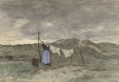 Vrouw bij een waslijn in de duinen